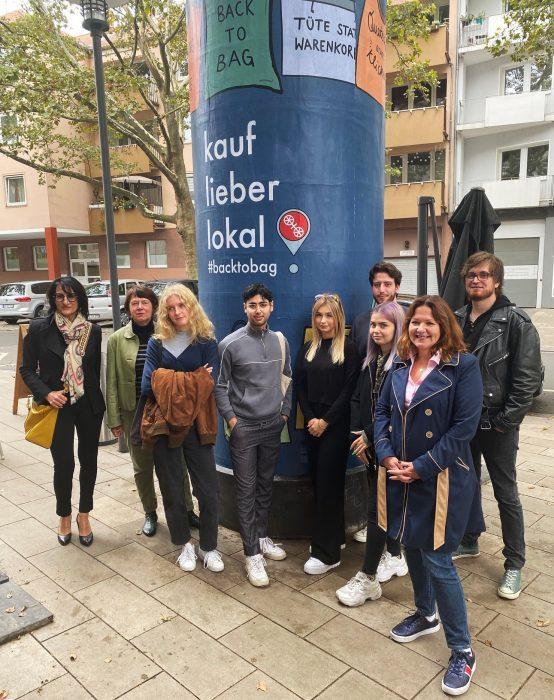 """Die Studierenden sowie Professorin Charlotte Schöner, die Wirtschaftsdezernentin Manuela Matz und  Christine Brücke von Ströer vor der Litfaßsäule """"kauf lieber lokal"""""""