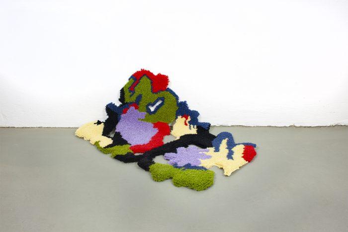 organisch geformter Teppich, halb an der Wand, halb auf dem Boden