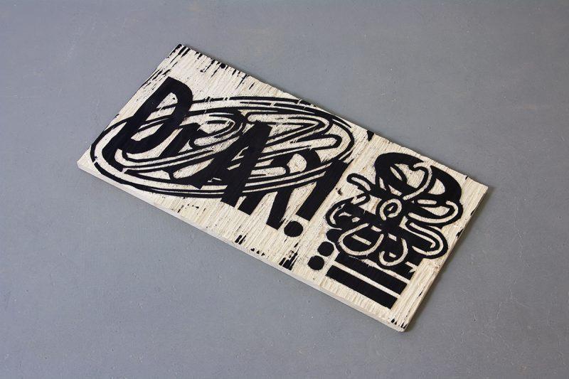 Holzschnittdruckplatte mit Schrift- und Grafikelementen