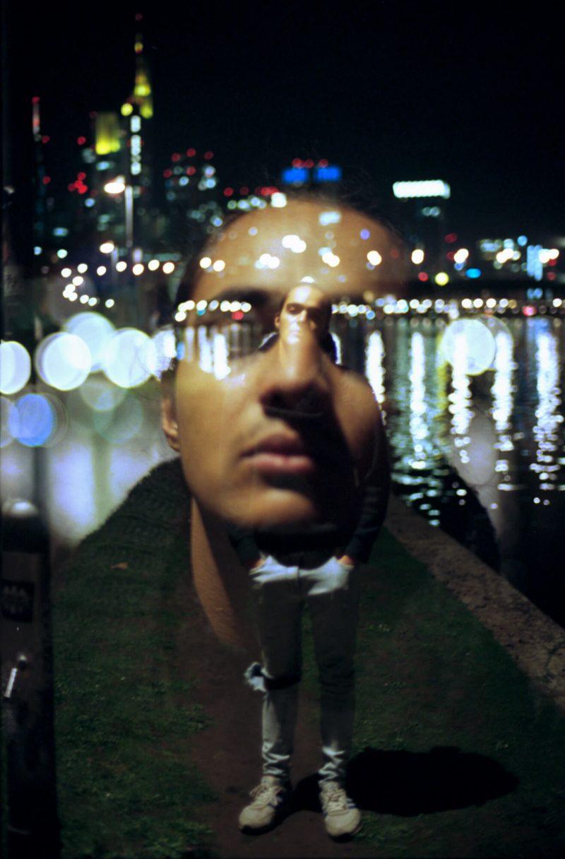 Ganzkörperportrait einer männlichen Person bei Nacht am Ufer, darauf eine durchsichtige Vergrößerung des Gesichts