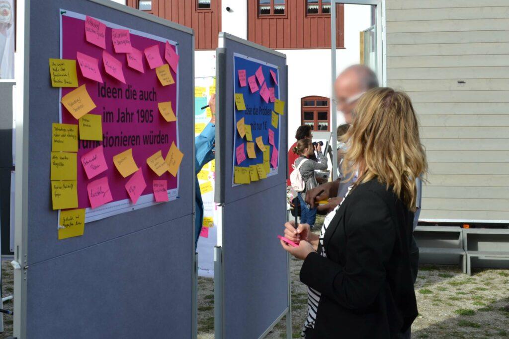 Zwei Personen stehen vor grauen Pinwänden, die mit gelben und pinken Notizzetteln bedeckt sind.