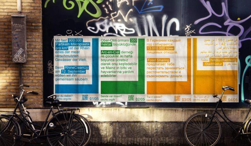 Vier Plakate an einer schwarzen Gebäudewand